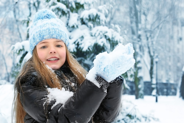 Śliczna mała dziewczynka bawi się śniegiem w winter park
