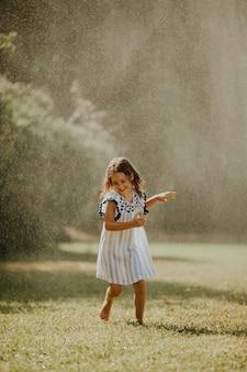 Śliczna mała dziewczynka bawi się wodą pod zraszaczem do nawadniania