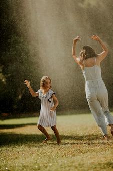 Śliczna mała dziewczynka bawi się wodą pod zraszaczem nawadniającym z matką