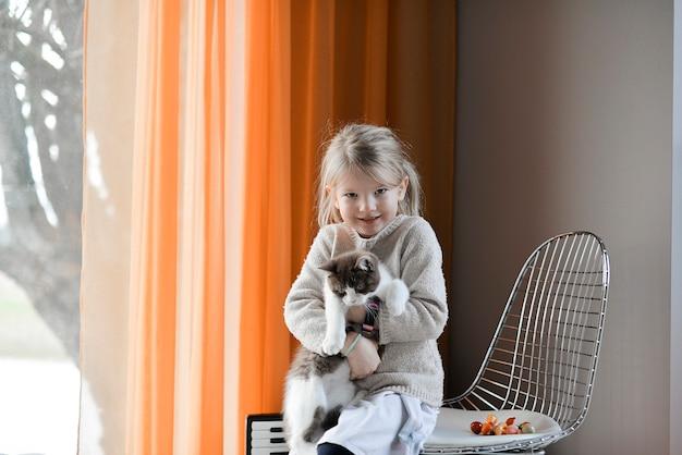 Śliczna mała dziewczynka bawi się z kotem w domu
