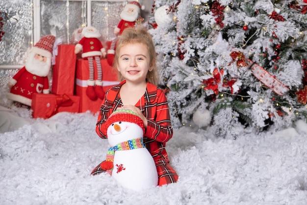 Śliczna mała dziewczynka bawi się zabawką bałwana w świątecznym pokoju. koncepcja wesołych świąt.