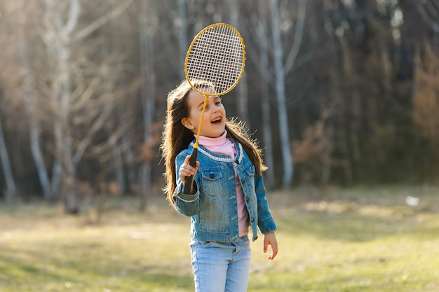 Śliczna mała dziewczynka bawić się badminton outdoors na ciepłym i pogodnym letnim dniu