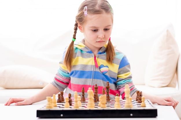 Śliczna mała dziewczynka bawić się szachy