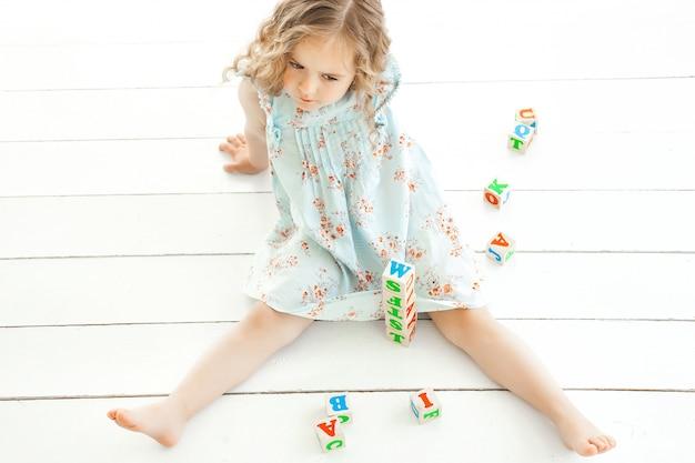Śliczna mała dziewczynka bawić się z abc sześcianami indoors