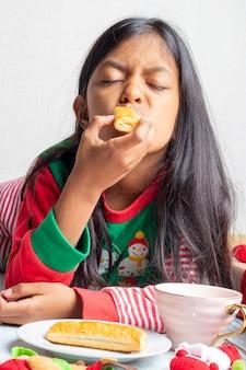 Śliczna mała dziewczynka bawić się z bożymi narodzeniami ciasteczka i mleko