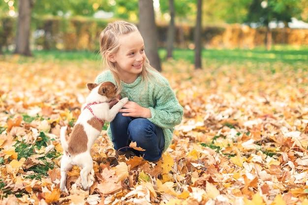 Śliczna mała dziewczynka bawić się z jej małym psem w jesień parku.