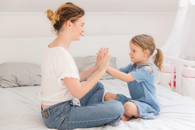 Śliczna mała dziewczynka bawić się z mamą w domu