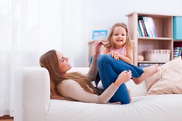 Śliczna mała dziewczynka bawić się z matką na kanapie