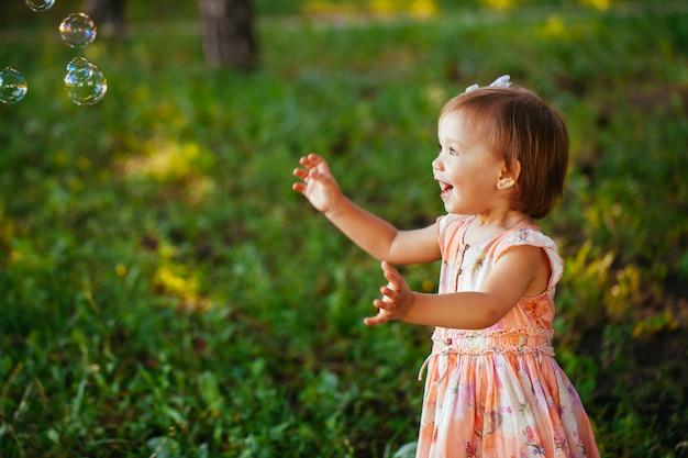 Śliczna mała dziewczynka bawić się z mydlanymi bąblami w parku.