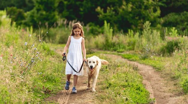 Śliczna mała dziewczynka biegnie z psem