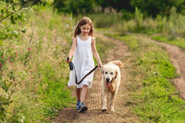 Śliczna mała dziewczynka biegnie z uroczym psem na drodze naziemnej w lecie