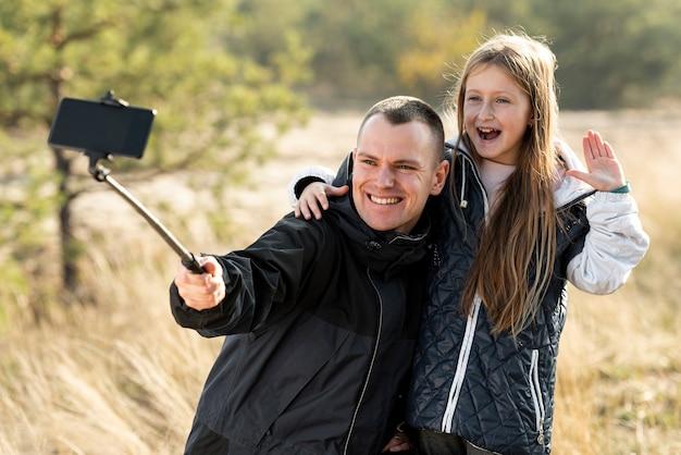 Śliczna mała dziewczynka bierze selfie z jej ojcem