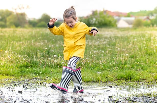 Śliczna mała dziewczynka chodzi po kałuży w jasnożółtym płaszczu przeciwdeszczowym i kaloszach w paski.