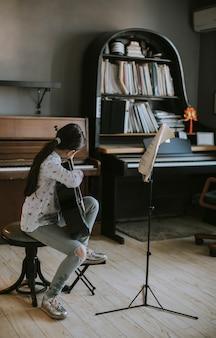 Śliczna mała dziewczynka ćwiczy na gitarze akustycznej w domu