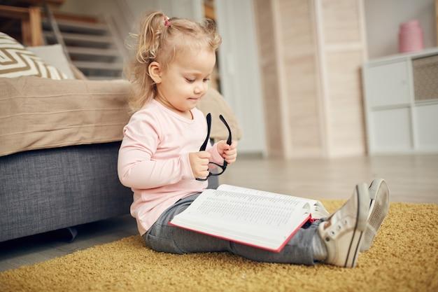 Śliczna mała dziewczynka czyta dużą książkę