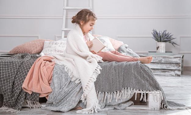 Śliczna mała dziewczynka czyta książkę na łóżku.