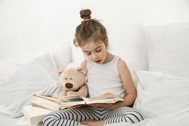 Śliczna mała dziewczynka czytając książkę na łóżku w sypialni.