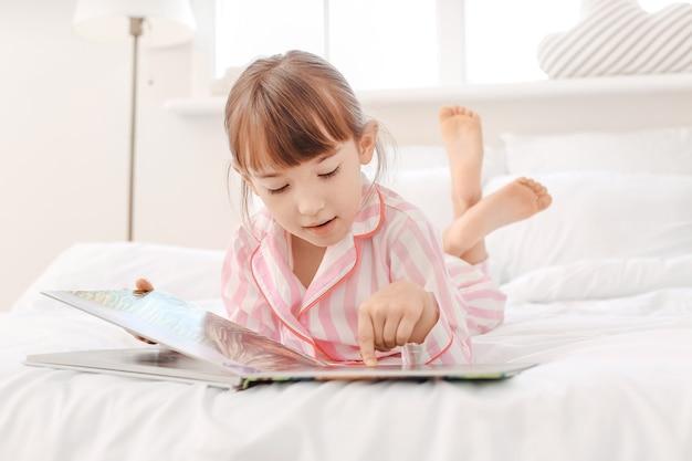Śliczna mała dziewczynka czytająca bajkę na dobranoc w domu