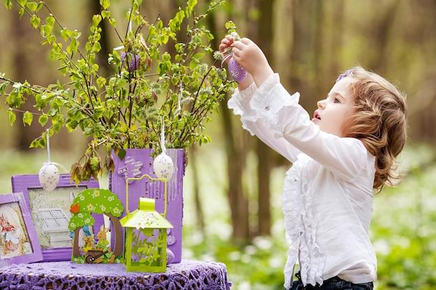 Śliczna mała dziewczynka dekorowanie gałęzi pisankami. wiosna w ogrodzie