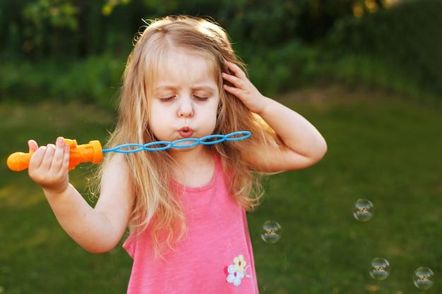 Śliczna mała dziewczynka dmucha bańki mydlane