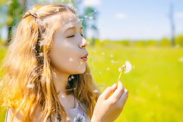 Śliczna mała dziewczynka dmucha daleko od dandelions w słonecznym dniu outdoors