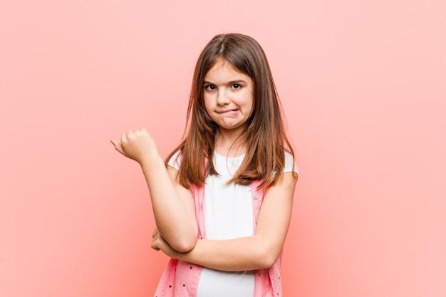 Śliczna mała dziewczynka dotyka tył głowy, myśleć i dokonuje wyboru.