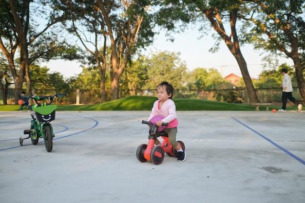 Śliczna mała dziewczynka dziecko uczy się jeździć na pierwszym rowerze równowagi dzieci na rowerze w parku
