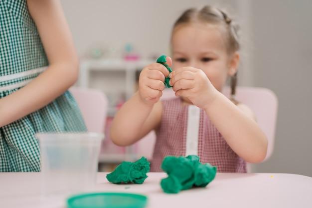 Śliczna mała dziewczynka foremki od plasteliny na stole