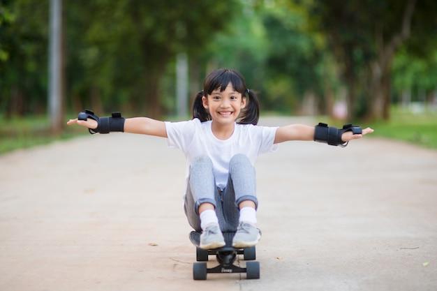 Śliczna mała dziewczynka gra na deskorolce lub surfuje w skate parku