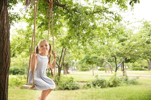 Śliczna mała dziewczynka gra na huśtawkach w parku