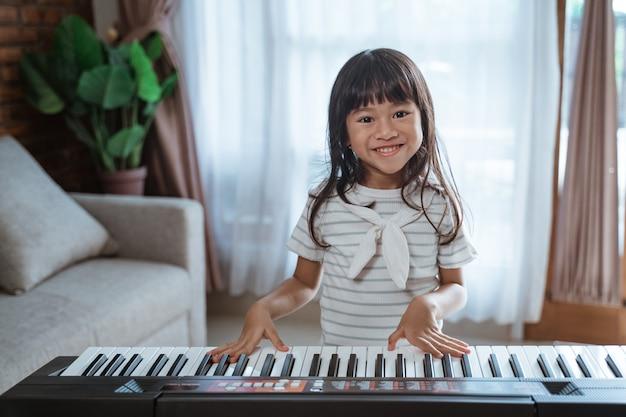 Śliczna mała dziewczynka gra na instrumencie klawiszowym