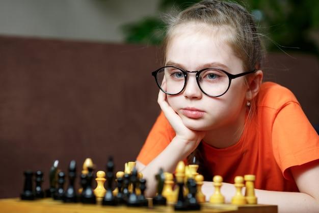 Śliczna mała dziewczynka gra w szachy w domu.