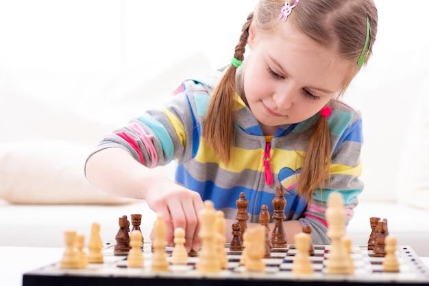 Śliczna mała dziewczynka gra w szachy