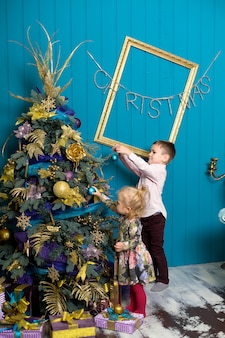 Śliczna mała dziewczynka i chłopiec dekorujemy choinki. brat i siostra w wigilię bożego narodzenia