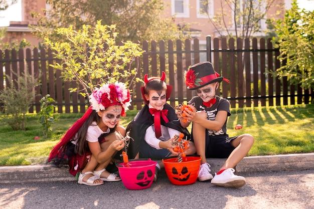 Śliczna mała dziewczynka i dwóch chłopców z pomalowanymi twarzami siedzą na zielonej trawie przed wiejskim domem i patrzą na halloweenowe smakołyki w koszach