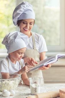 Śliczna mała dziewczynka i jej piękna mama czytają przepis.