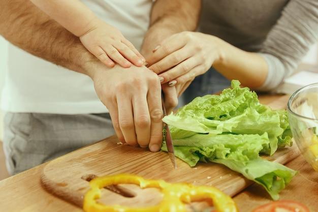 Śliczna mała dziewczynka i jej piękni rodzice kroją warzywa i uśmiechają się, robiąc sałatkę w kuchni w domu
