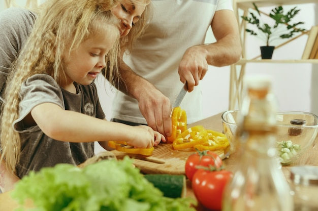 Śliczna mała dziewczynka i jej piękni rodzice krojenia warzyw i uśmiechają się, robiąc sałatkę w kuchni w domu. koncepcja stylu życia rodziny