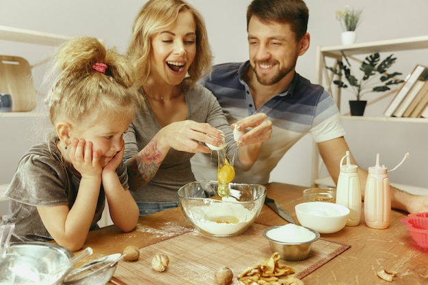 Śliczna mała dziewczynka i jej piękni rodzice przygotowują ciasto na ciasto w kuchni w domu. koncepcja stylu życia rodziny