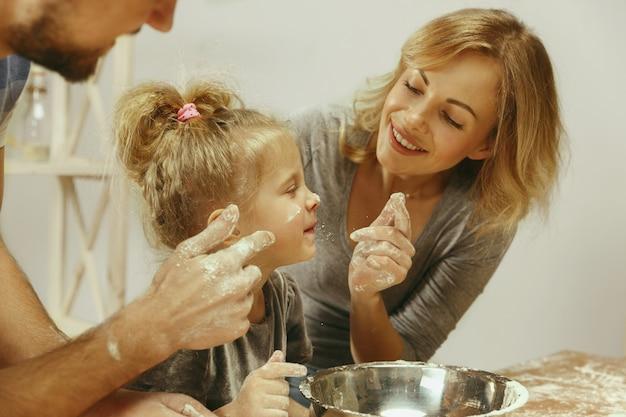 Śliczna mała dziewczynka i jej piękni rodzice przygotowują ciasto na ciasto w kuchni w domu