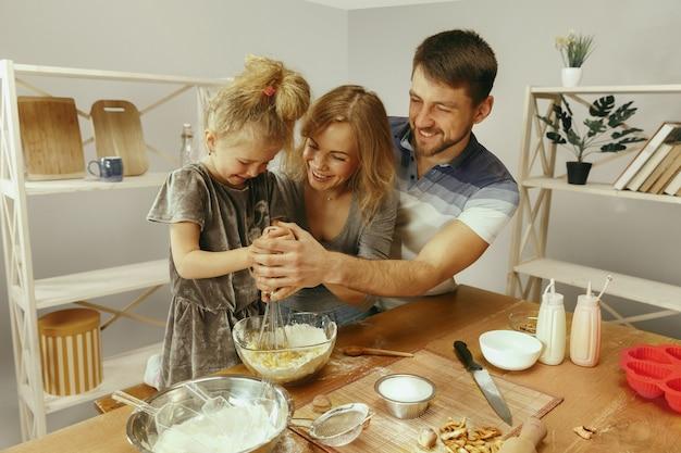 Śliczna mała dziewczynka i jej piękni rodzice przygotowują ciasto na ciasto w kuchni w domu.