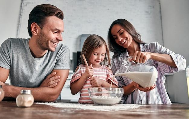 Śliczna mała dziewczynka i jej piękni rodzice wyrabiają mąkę do pieczenia i uśmiechają się podczas gotowania w kuchni.