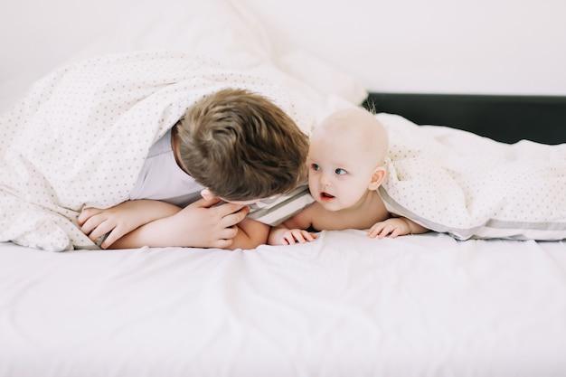 Śliczna mała dziewczynka i jej starszy brat leżą pod kocem w łóżku