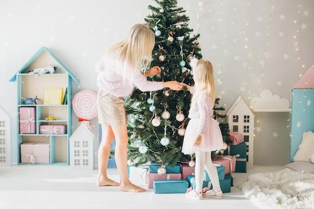 Śliczna mała dziewczynka i mama z blond włosami ubierają choinkę