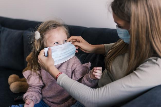 Śliczna mała dziewczynka i matka jest ubranym twarzy maskę, siedzi na łóżku w domu, pociesza smutnej przedszkolnej córki