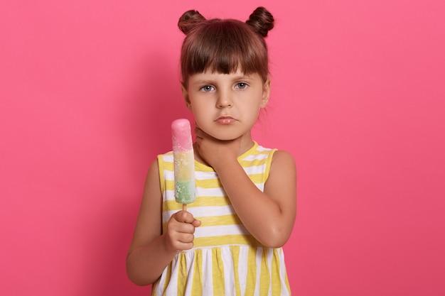 Śliczna mała dziewczynka je lody i ma ból gardła