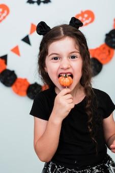 Śliczna mała dziewczynka je pumpking cukierek