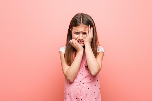 Śliczna mała dziewczynka jęczy i płacze nieszczęśliwie.