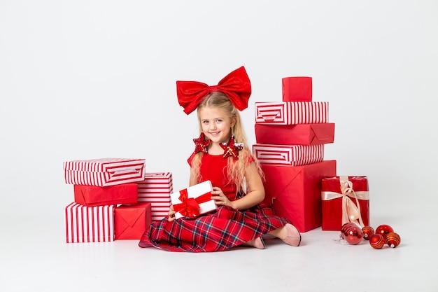 Śliczna mała dziewczynka jest rozważana na boże narodzenie. białe tło, duże pudełka na prezenty, miejsce na tekst. pojęcie bożego narodzenia