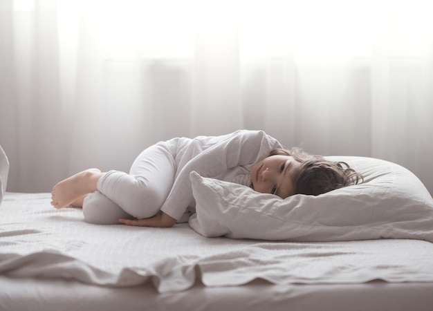 Śliczna mała dziewczynka jest smutna leżąc w białym wygodnym łóżku, koncepcja odpoczynku i snu dzieci